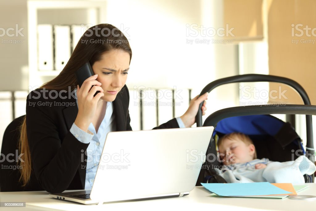 Stressed mother working taking care of her baby at office stock photo