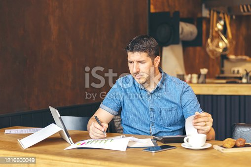 Mature small business owner calculating taxes due to crisis of pandemic quarantine – Stressed entrepreneur using laptop and calculator to work and calculate financial expenses of new business start-up