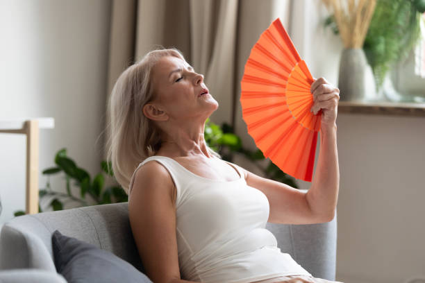 Stressed old woman waving fan suffer from overheating at home stock photo