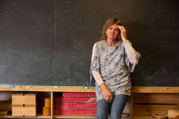 A stressed or depressed mature teacher in a classroom. stock photo