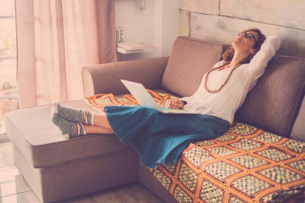 estresado mujer hermosa edad media trabajando en ordenador portátil en el sofá en casa. oficina alternativa de internet para trabajador de digital en línea. cansado de buscar en la parte superior, usando graciosos calcetines - social media fotografías e imágenes de stock
