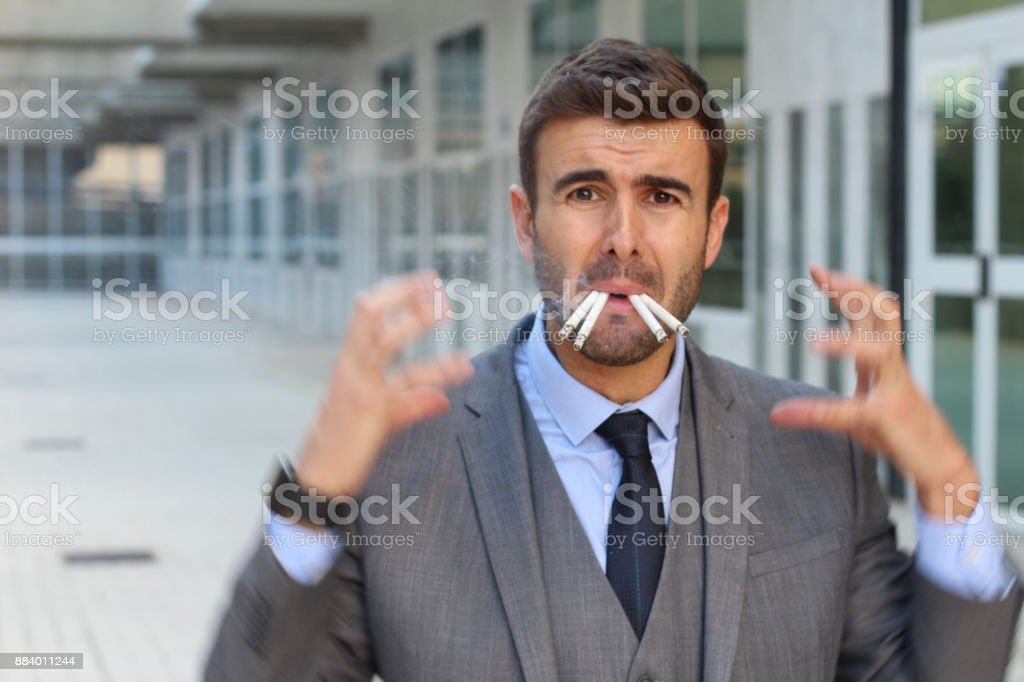 Stressed out businessman smoking four cigarettes stock photo