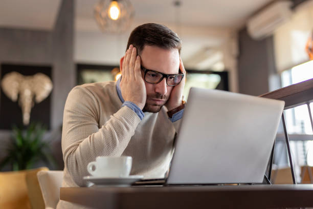 Stressed out businessman working on a laptop computer stock photo