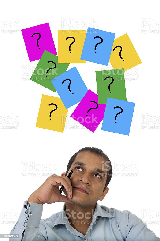 Stressed out Indian businessman against question mark signs royalty-free stock photo