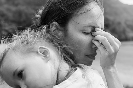 A sad mother covering her face depressed and unhappy holding her child in black and white.
