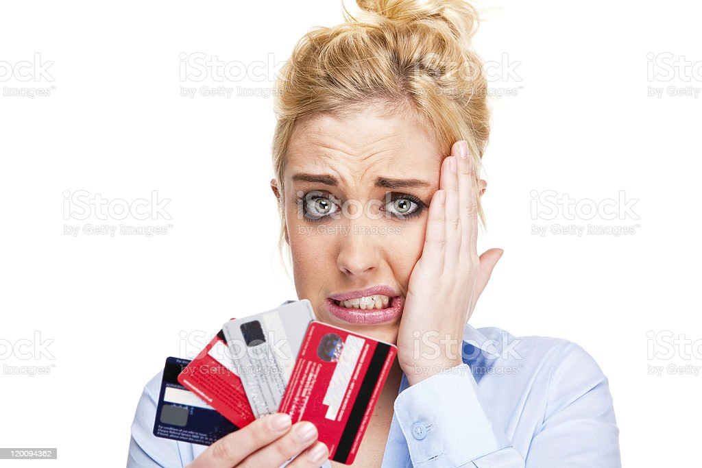 Stressed out woman holding up four credit cards stock photo