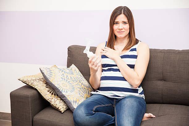 Stressed pregnant woman with breast pump - foto de acervo