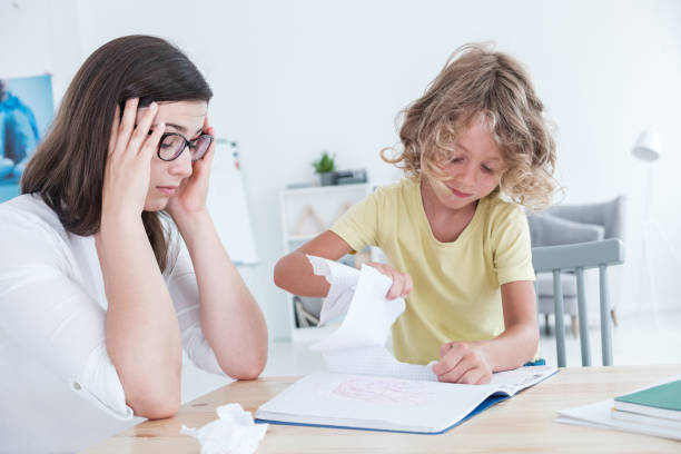 Stressed psychotherapist having a headache during a meeting with a rebellious child with behavioral disorders. The kid is tearing sheets of paper from the notebook. stock photo
