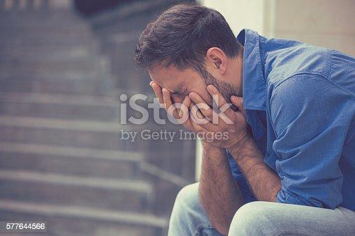 istock stressed sad crying man sitting outside 577644566
