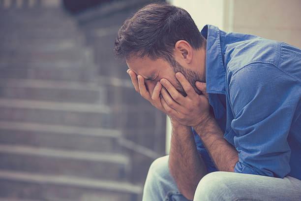stressed sad crying man sitting outside stock photo