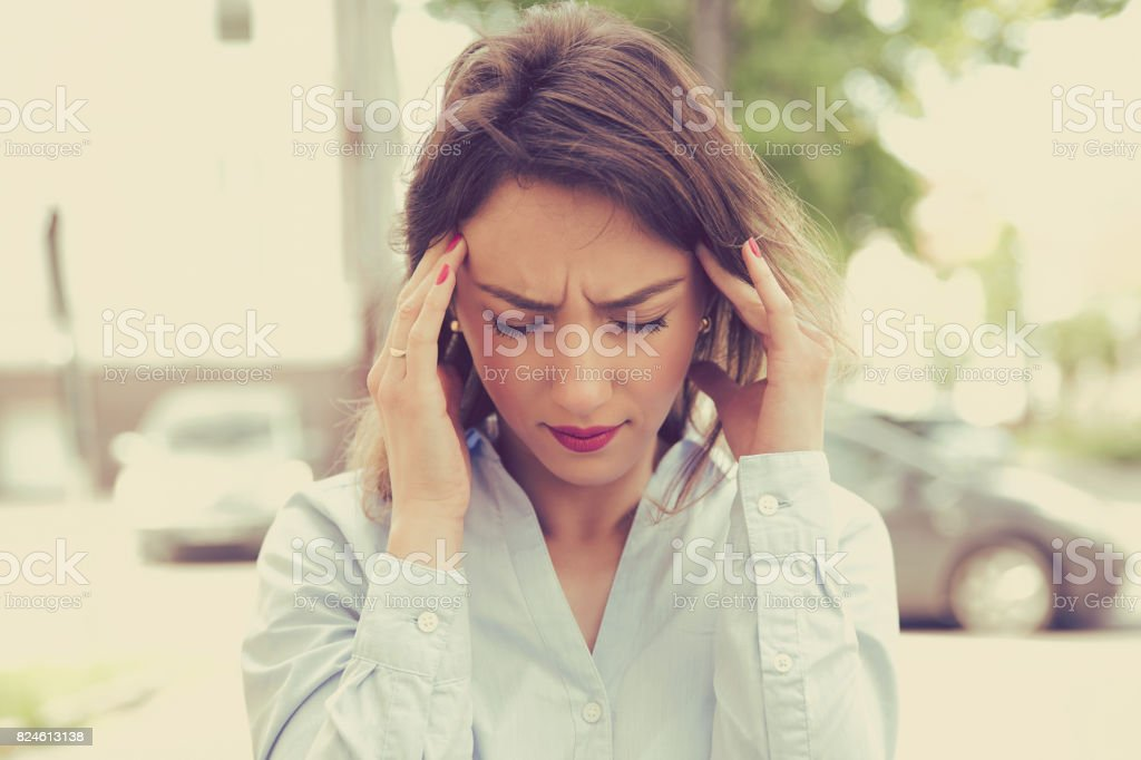 stressed sad young woman standing outdoors. City life style stress stock photo