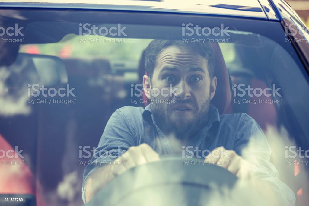 Stressed scared young man driver. Inexperienced anxious motorist concept stock photo
