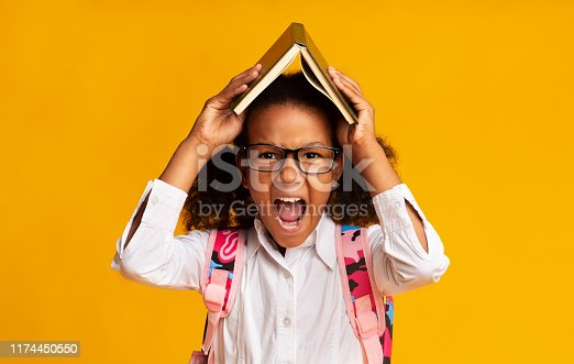 istock Stressed Schoolgirl Screaming Covering Head With Book Over Yellow Background 1174450550