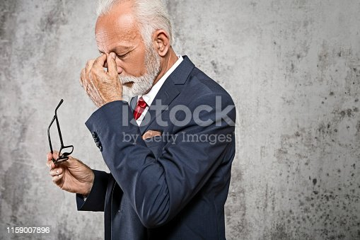 626964348istockphoto Stressed senior businessman rubbing eyes 1159007896