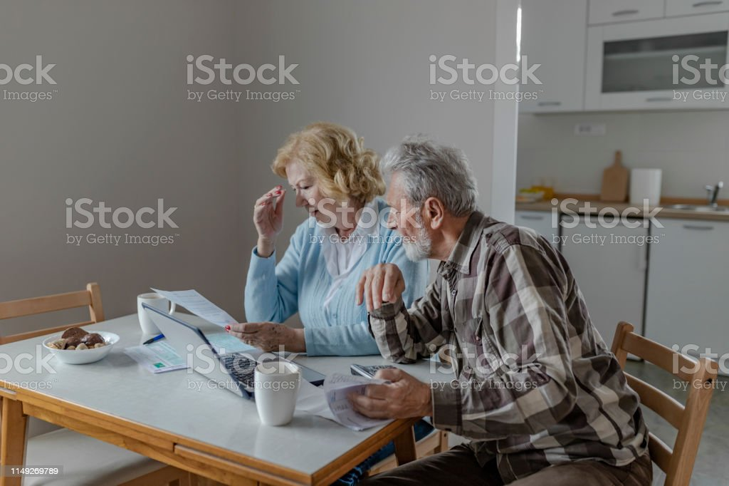 Serious Worried Senior Couple Calculating Bills to Pay or Checking...
