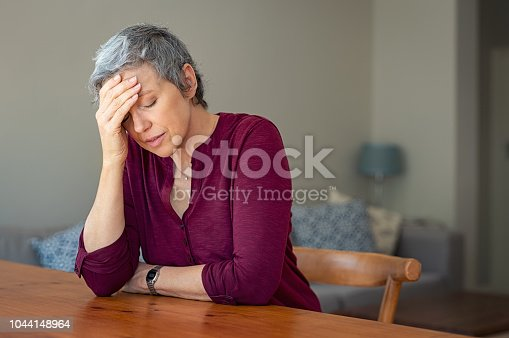 Senior woman suffering from headache while sitting at table in a living room. Depressed mature woman with head in hand thinking. Stressed old lady suffering from migraine at home.