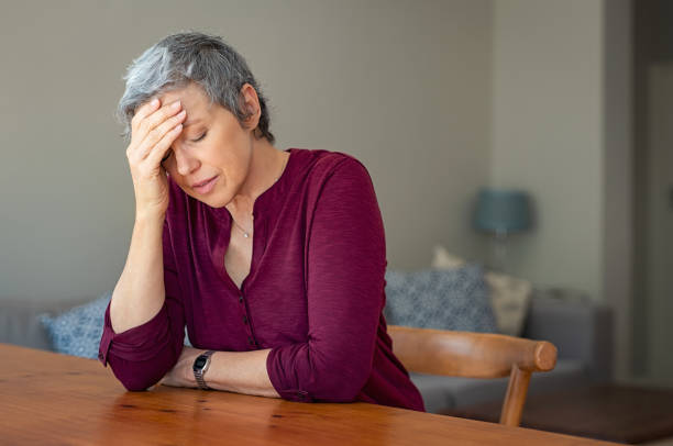 Stressed senior woman at home Senior woman suffering from headache while sitting at table in a living room. Depressed mature woman with head in hand thinking. Stressed old lady suffering from migraine at home. 60 64 years stock pictures, royalty-free photos & images