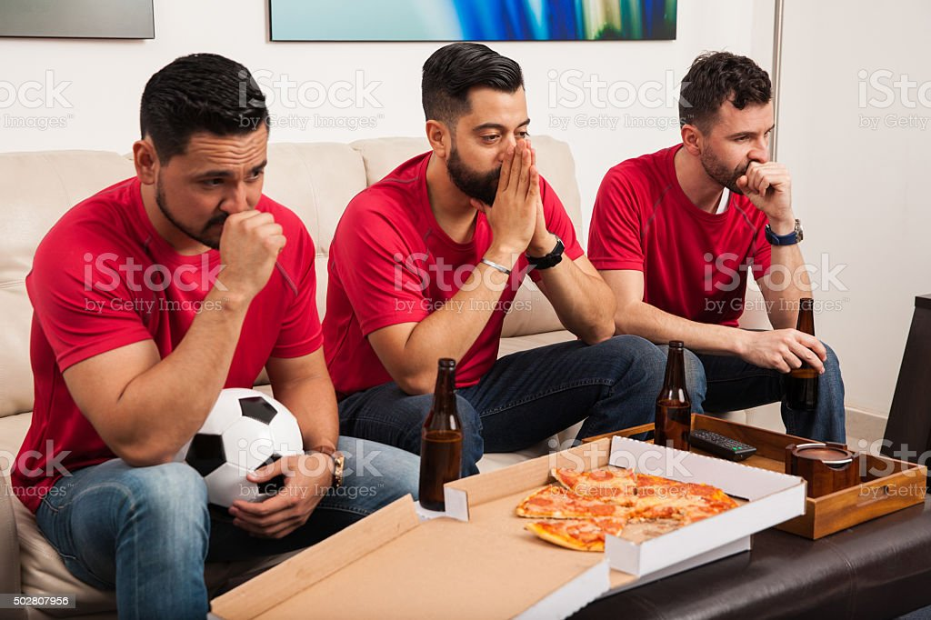 Stressed soccer fans watching a game stock photo