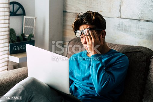 Stressed student at home studying with personal laptop computer - tired teenager for school work -internet. addiction for game or job search concept - indoor technology activity