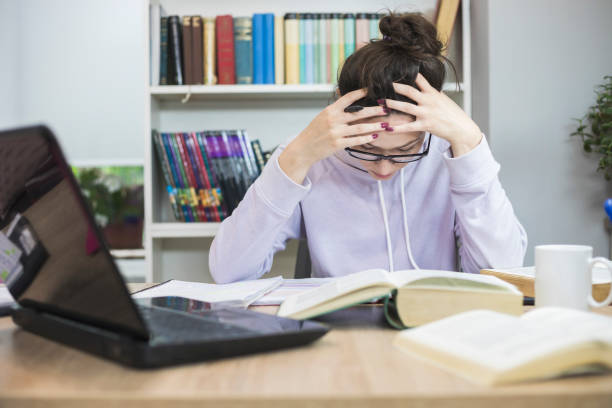 Stressed Student Doing Homework At The Desk stock photo