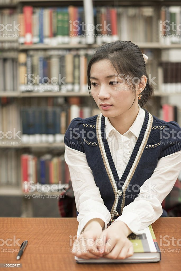 Stressed student sitting at a desk in library royalty-free stock photo