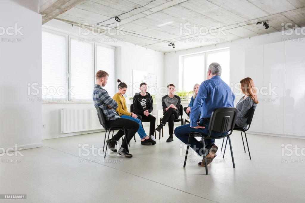 Stressed students sharing problems during meeting Stressed students sharing problems during meeting. Social worker is explaining young men and women in lecture hall. They are in group therapy at university. 18-19 Years Stock Photo