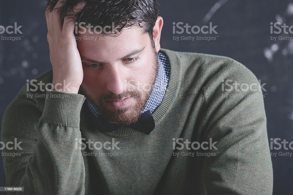 Stressed teacher man wearing stylish clothes in front a blackboard. stock photo
