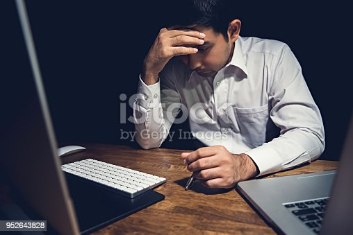 istock Stressed tired young man feeling headache while working overtime  at night 952643828