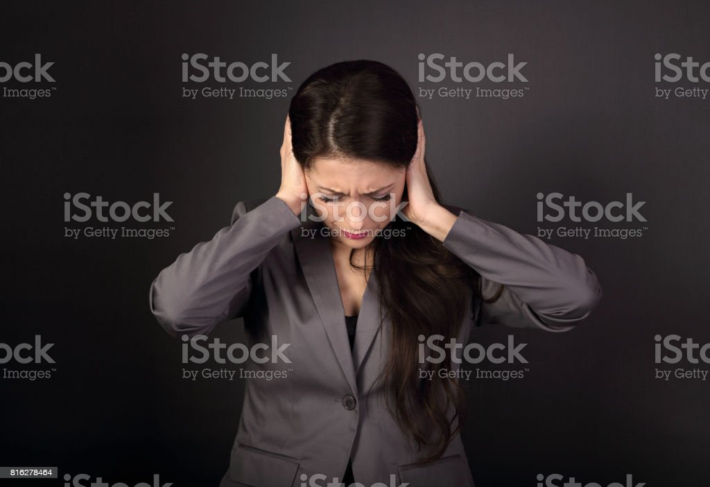 Stressed unhappy business woman in grey suit closed ears the hands because not want the hear any sounds and noise on dark grey background stock photo