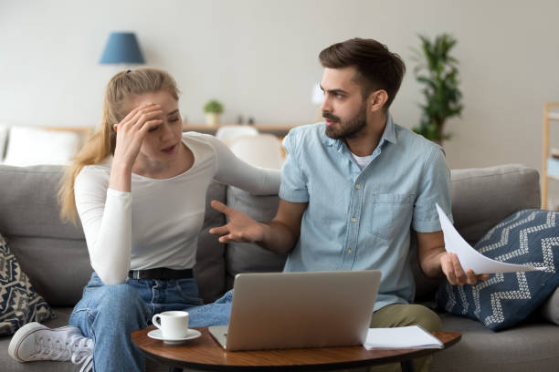 stressed unhappy couple arguing about expenses with laptop and papers - bills couple imagens e fotografias de stock