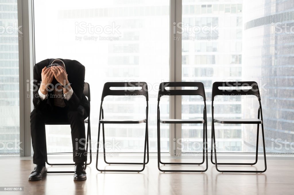Stressed upset businessman sitting on chair, received bad news. stock photo