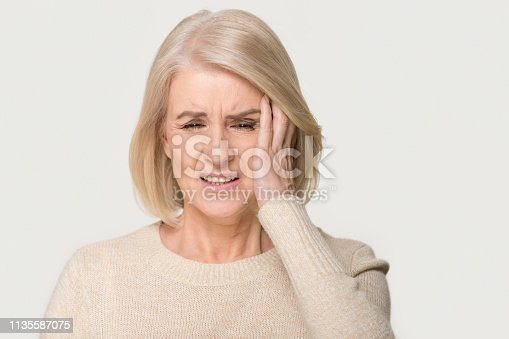Stressed upset middle aged old woman suffering from terrible headache concept, sad tired sick senior mature lady feeling dizzy having migraine pain isolated on white grey blank studio background