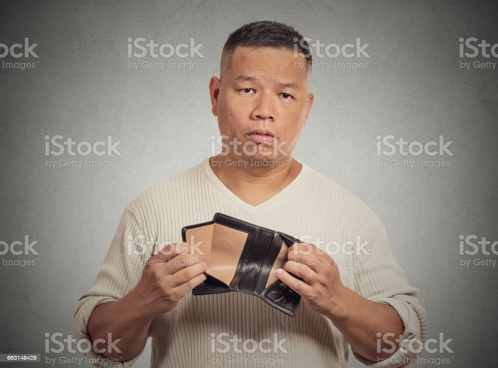 stressed, upset, sad, unhappy middle aged  man standing with, holding empty wallet stock photo