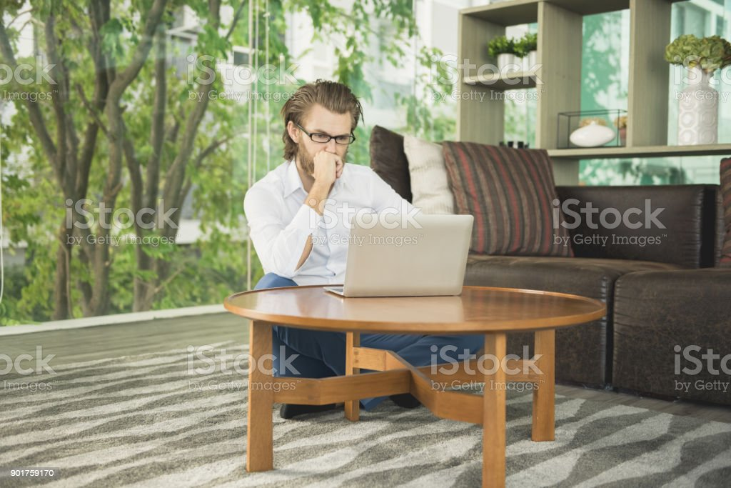 Stressed western businessman using a laptop in living room stock photo