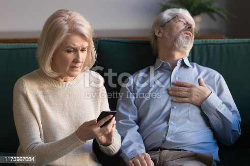 istock Stressed wife calling 911 for rescue senior husband heart attack 1173667034