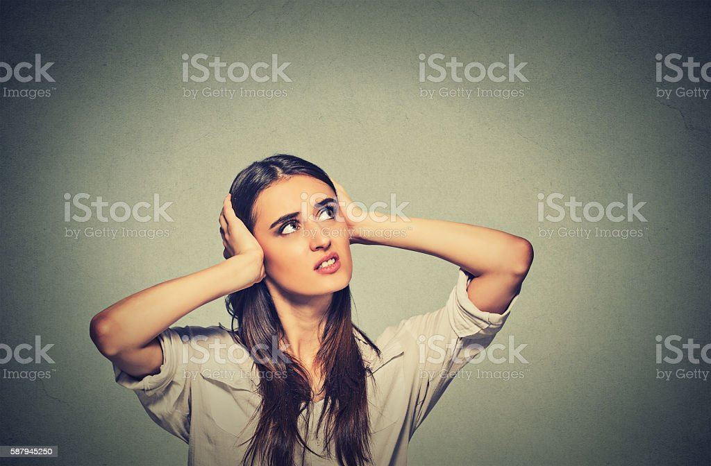 stressed woman covering ears looking up loud noise upstairs stock photo