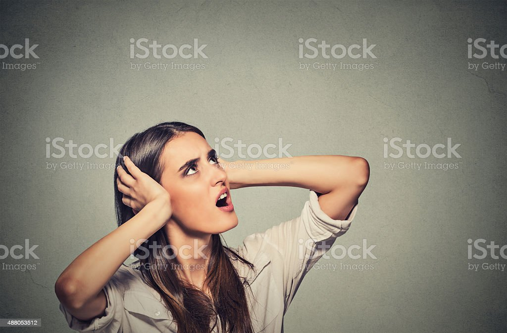 stressed woman covering ears looking up noise upstairs stock photo