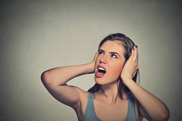 ストレスのたまった女性は彼女の耳を見上げるカバー ストックフォト