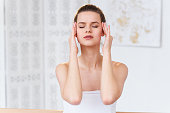 istock Stressed woman has a strong headache. Close up portrait of beautiful girl suffering from head migraine. Feeling pressure and stress. 1207331298