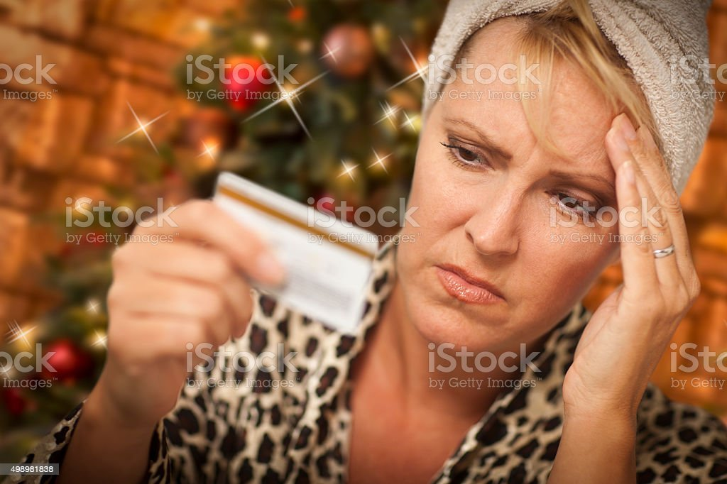 Stressed Woman Holding Credit Card In Front of Christmas Tree stock photo