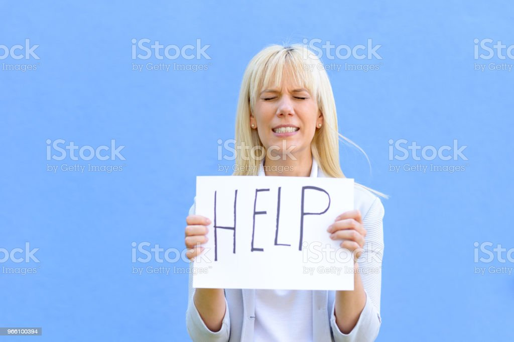 Stressed woman holding up a help sign - Royalty-free Adult Stock Photo