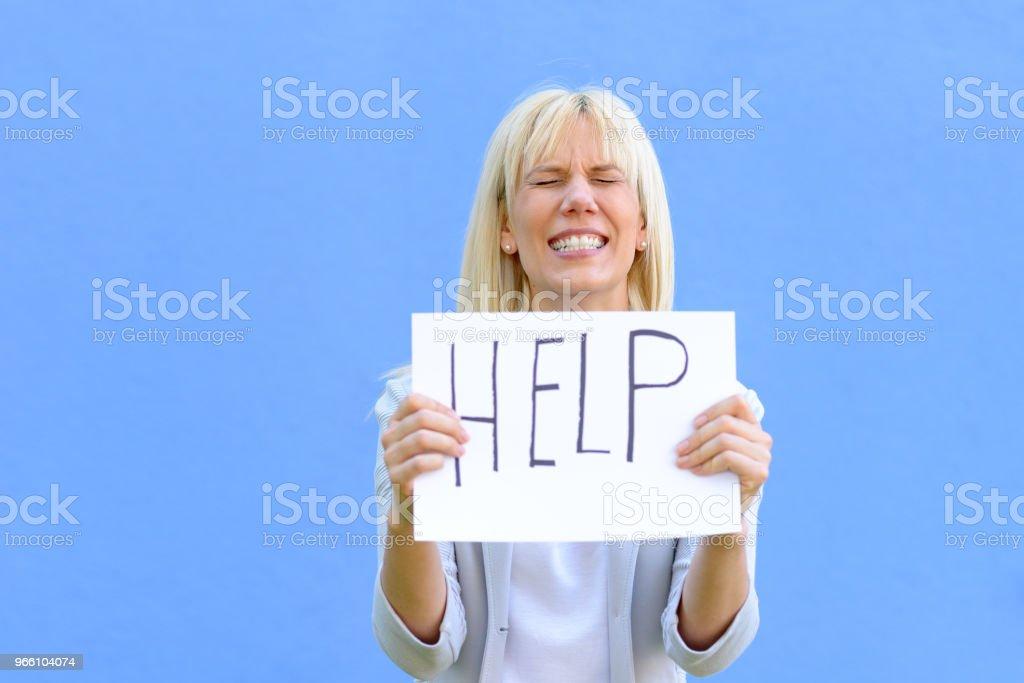 Betonte Frau hält ein Schild mit Hilfe - Lizenzfrei Attraktive Frau Stock-Foto
