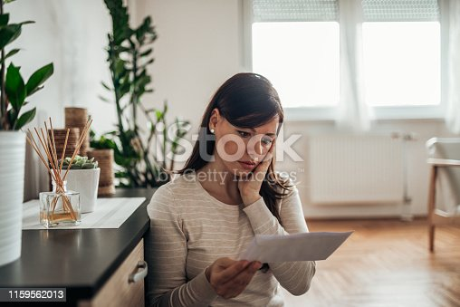 Stressed woman reading a letter at home.