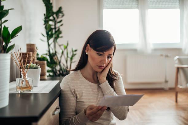 Mujer estresada leyendo una carta en casa. - foto de stock
