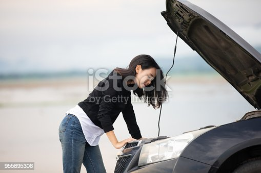 istock Stressed woman sitting after a car breakdown with Red triangle of a car on the road 955895306
