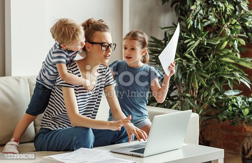 Tired young mother sitting on sofa and working with laptop and documents while little kids having fun and making noise