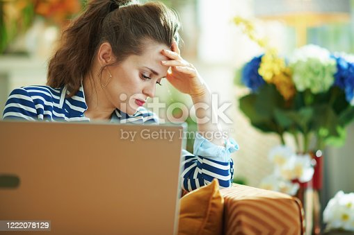 513396643 istock photo stressed woman with laptop in modern house in sunny day 1222078129