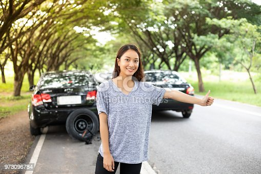 860373412 istock photo Stressed women  after a car breakdown with Red triangle of a car on the road 973096784