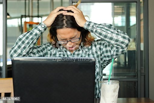 833210686 istock photo Stressed young Asian business man with hands on head feeling tired against his work in office. Exhausted and overwork job concept. 687975962