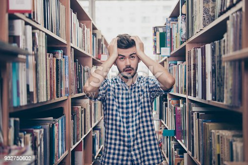 istock Stressed young brunet bearded student`s brain is blasting, he stands between the book shelves in the library, tired shocked grimace, holding the head, too much information! Exam is soon 932750602